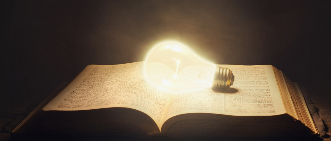 Surreal image of a glowing light bulb in an open Bible.
