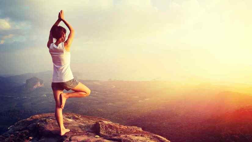 woman mountain peak cliff practice yoga